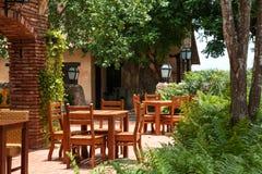 Trätabeller i en tropisk restaurang Arkivbild