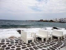 Trätabeller nästan i havet, Paros ö, Grekland Arkivfoto