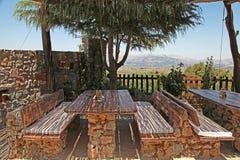 Trätabeller och bänkar i det lantliga utomhus- kafét, Grekland Royaltyfri Fotografi