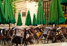 Trätabeller och stolar på stadsbakgrund, sommarkafébegrepp med gröna paraplyer utomhus, kopieringsutrymme royaltyfri foto