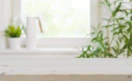 Trätabletop med kopieringsutrymme över suddig kökfönsterbakgrund royaltyfri fotografi