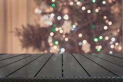 Trätabletop och suddigt julträd i inre Xmas-bakgrund för skärm dina produkter royaltyfri bild