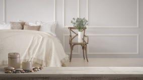 Trätappningtabellöverkant eller hylla med stearinljus och kiselstenar, zenlynne, över klassiskt sovrum för suddig tappning med mj arkivbilder