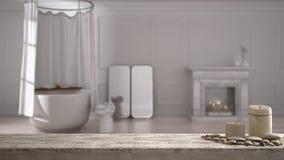 Trätappningtabellöverkant eller hylla med stearinljus och kiselstenar, zenlynne, över suddigt klassiskt badrum med badkaret och s royaltyfria foton