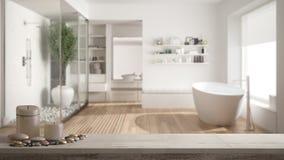 Trätappningtabellöverkant eller hylla med stearinljus och kiselstenar, zenlynne, över suddigt minimalist badrum med duschen och g royaltyfri bild