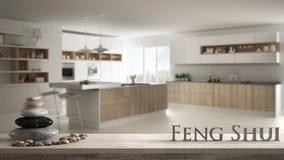 Trätappningtabellhylla med kiselstenjämvikt och bokstäver som 3d gör ordfengshuien över suddigt modernt vitt kök med att uppvakta royaltyfri bild