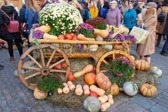 Trätappningvagn som dekoreras med pumpor och blommor Exponering av pumpor, garnering av vita och röda blommor arkivfoton