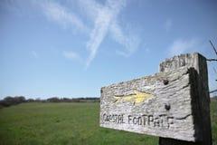Träteckenstolpe för kust- vandringsled med pilen mot en blå himmel Royaltyfria Bilder
