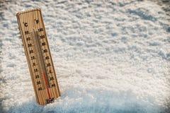 Trätermometer i snön med att frysa temperaturer Arkivfoton