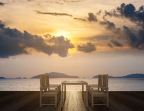 Träterrass med att äta middag tabellen och stolar på tropisk havsikt i solnedgång Arkivfoton