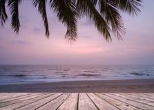Träterrassen över den tropiska östranden med kokosnöten gömma i handflatan på solnedgång- eller soluppgångtid Royaltyfri Fotografi