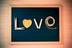Trätorkdukepinnor, pappers- formhjärta, repslag ordet FÖRÄLSKELSE på det svarta brädet för valentindag Royaltyfri Bild