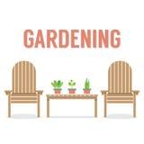 Träträdgårds- stolar och krukväxt på tabellen Arkivfoto