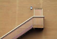 Trätrappa som leder till en dörr i mitt av en vägg Arkivbild