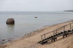 Trätrappa som leder till en tom strand Arkivfoto