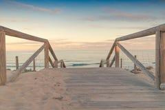 Trätrappuppgång- och räcketillträde till strandsanden på solnedgången Fotografering för Bildbyråer