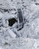 Trätrappuppgång som frysas i is som täckas med istappar mot ett djupfryst lavafält som täckas med is och snö arkivbild