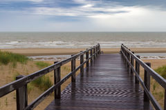 Trätrappuppgång som leder in i stormig himmel och havet på De Haan, Bel Royaltyfri Bild