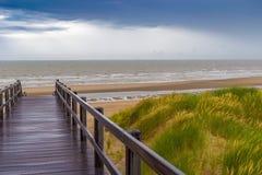 Trätrappuppgång som leder in i stormig himmel och havet på De Haan, Belgien Arkivfoto