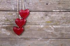Trätre röda hjärtor Arkivfoton