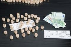 Trätrummalotto, kort och euro Svart trätabell Arkivfoton
