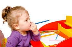 Träume und Bisse des kleinen Mädchens ein Bleistift beim Sitzen an einem Tisch, lokalisiert auf einem weißen Hintergrund Stockfotografie