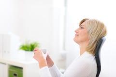 Träumen der älteren Geschäftsfrau mit Cup Stockfoto