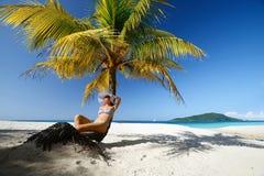 Träumen der Frau, die auf dem Strand unter einer Palme auf einem Beaut sitzt Lizenzfreies Stockfoto