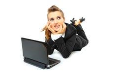 Träumen der Geschäftsfrau, die Laptop auf Fußboden verwendet Stockbilder