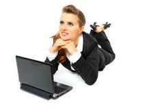 Träumen der Geschäftsfrau, die Laptop auf Fußboden verwendet Stockfotografie