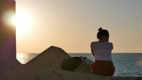 Träumen der jungen Frau, die auf den Felsen nahe dem Meer bei Sonnenuntergang sitzt Stockfotos