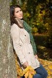 Träumen der jungen Frau, die auf einem Baumstamm im Fall sich lehnt Lizenzfreie Stockfotos