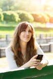 Träumen der jungen Schönheit mit Telefon auf Bank Lizenzfreie Stockbilder