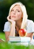 Träumen der Studentin, die auf dem Gras nahe dem Stapel von Büchern liegt Stockfotos