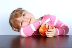 Träumen des kleinen Mädchens mit Apfel Lizenzfreie Stockfotos