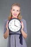 Träumen des Pinupmädchens in gestreiftem Kleid mit Uhr Stockfotos