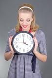 Träumen des Pinupmädchens in gestreiftem Kleid mit Uhr über Grau Lizenzfreie Stockfotografie