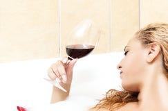 Träumen kaukasisches weibliches blondes im Bad, das mit Glas R sich entspannt Stockfotografie