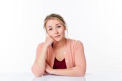 Träumende schöne blonde Frau 20s, die am spärlichen Schreibtisch sitzt Lizenzfreies Stockbild