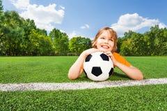 Träumender Junge hält Fußball und schaut und Legen Lizenzfreies Stockbild