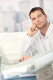 Träumender junger Mann, der am Schreibtisch sitzt Lizenzfreie Stockfotografie