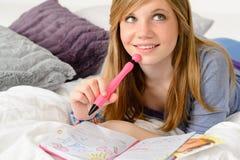 Träumendes Jugendlichmädchen, das ihre Zeitschrift schreibt Stockbilder