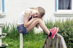 Träumendes Mädchen, das allein auf der Brücke sitzt Lizenzfreie Stockfotos