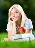Träumendes Mädchen, das auf dem Gras nahe dem Stapel von Büchern liegt Lizenzfreies Stockbild