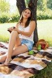 Träumendes Mädchen, das mit einem Buch im Garten sitzt Lizenzfreie Stockfotos