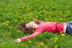 Träumendes Mädchen, das unter Löwenzahn liegt Lizenzfreie Stockfotografie