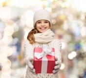 Träumendes Mädchen in der Winterkleidung mit Geschenkbox Stockfotos