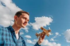Träumer, junger Mann, der in der Hand hölzernes Spielzeugflugzeug am Hintergrund des blauen Himmels mit Kopienraum hält Lizenzfreies Stockbild