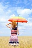 Träumerfrau mit Regenschirm auf dem Weizengebiet an Stockbilder