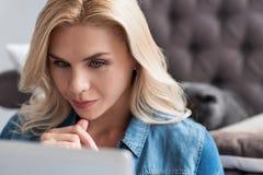 Träumerische blonde Frau, die Laptop umarmt Stockbilder